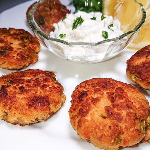 how to make fish cakes- fish cakes in a ceramic plate with a bowl of yogurt dip.