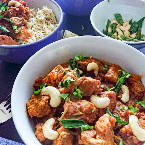 easy recipe for mutton curry- goat meat curry served with rice in ceramic bowls.