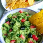 guacamole with berries in a bowl and tortilla chips
