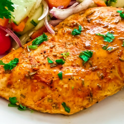 closeup view of oven baked chicken breast served with garden salad in a white ceramic plate