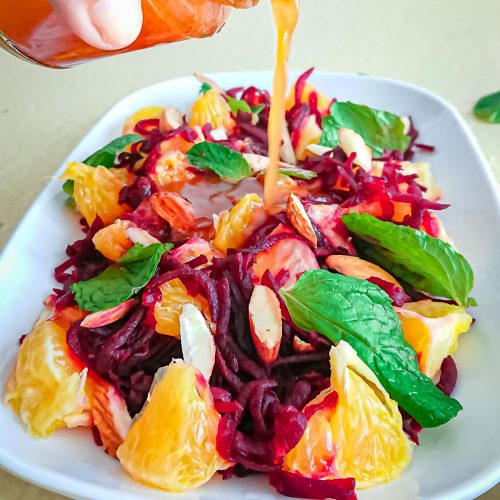 closeup view of orange juice dressing being poured on beet and orange salad